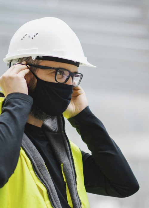 Portrait Of Delivery Driver Wearing Mask Holding Package Outside House