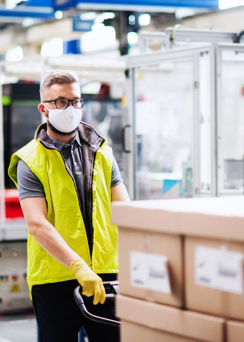 Portrait of man worker with protective mask working in industrial factory or warehouse.